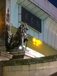 "The plaque reads ""Nihonbashi"", the name of the bridge. Though I should clarify Nihonbashi is the bridge these statues are on, not the overpasses above. (May 2016)"