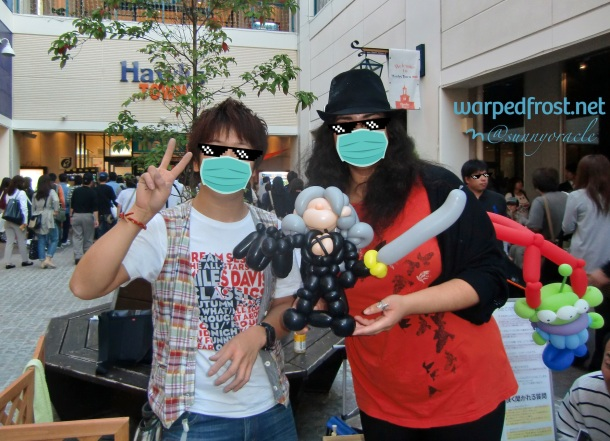 Photo of the balloon artist and I posing with Balloon Seph between us. The artist chose to depict Seph with his One Wing and Masamune.