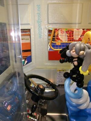 """Balloon Seph in a """"truck"""" in an amusement center."""