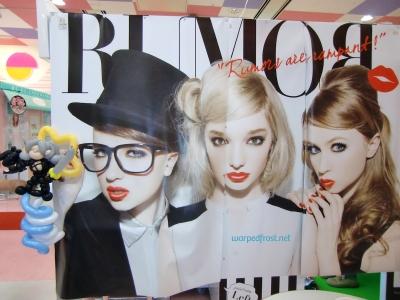 "Balloon Seph next to a purikura (photobooth) that says ""Rumors are rampant!"" and shows three glamorous blonde girls"