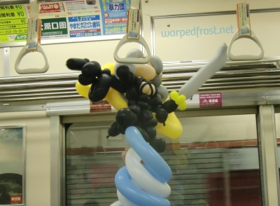 Balloon Seph hanging on to a strap on the train