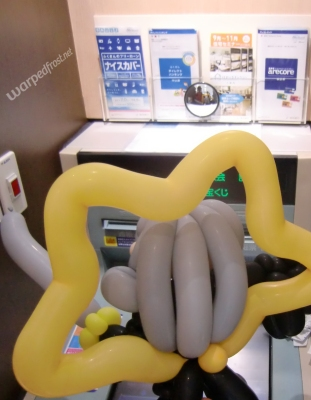 Balloon Seph seen from behind as he studies a Fukuoka Bank ATM