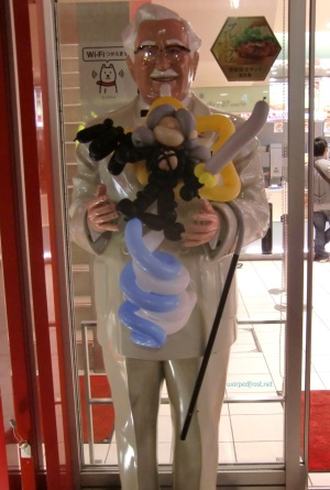 Balloon Seph in the arms of a statue of Colonel Sanders outside of a KFC