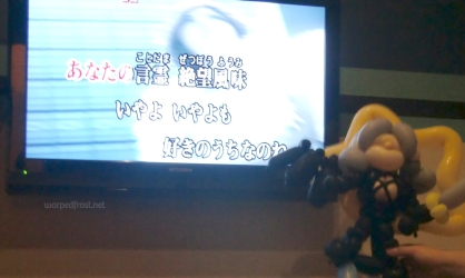 "Balloon Seph in front of a TV screen in the karaoke room with the lyrics to ""Zessei Bijin"" from the anime ""Sayonara Zetsubou Sensei,"" which includes the word ""despair"" (zetsubou) in the lyrics."
