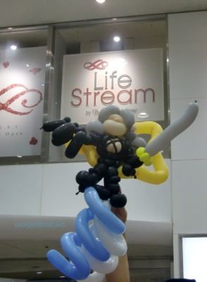 "Balloon Sephiroth in front of a store window for ""Life Stream by Ohga Pharmacy"""