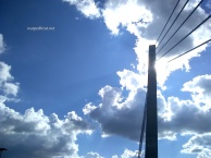 The tower of the Bagley Pedestrian Bridge in Detroit stands silhouetted against a bank of fluffly, sun-lit clouds in a blue sky.