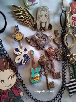 """Close up of an """"ita bag,"""" a bag full of fandom pins and chotchkis. This one has mostly Hard Rock Cafe pins and FFVII keychains."""