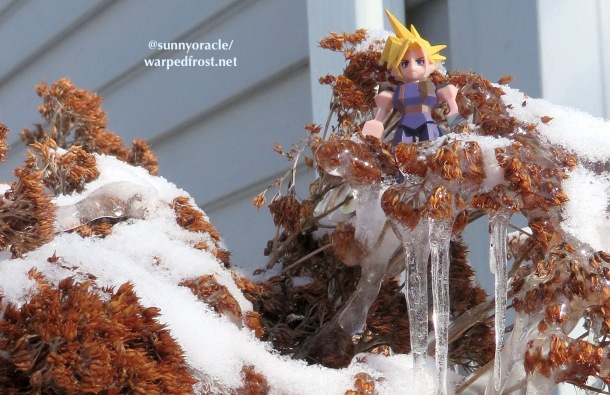 A Cloud Strife Polygon figure stands in a branch of dried sedum which as frozen over. There is powdery snow on top of the sedum, and icicles hanging down below. Some of the dried flowers are encased in ice.