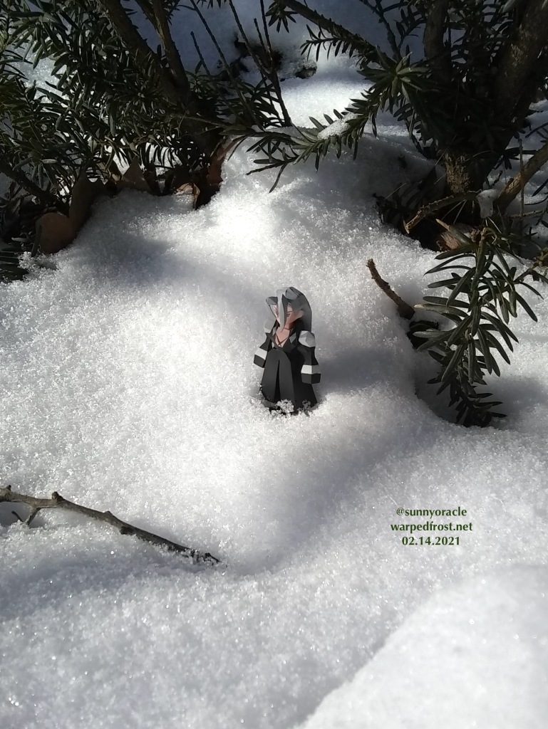 The Sephiroth Polygon figure standing in powdery snow beneath a Japanese yew.